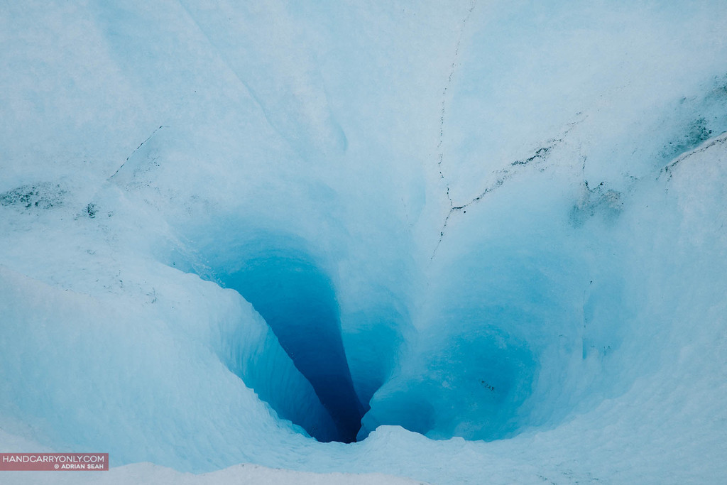 the melting ice flows into deep blue sinkholes