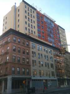  The Gateway Condominium in Harlem completely visible, a tri colored building appears