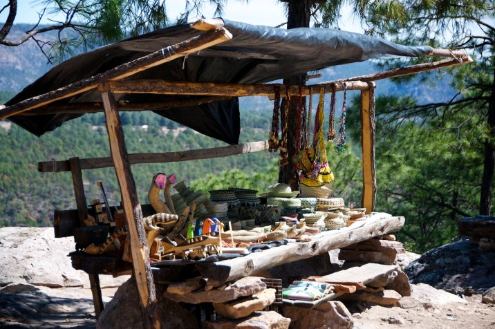 Tarahumara crafts for sale at the edge of a canyon rim.