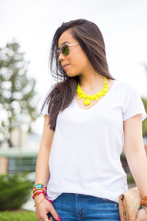 An Dyer wearing ShopLately Glint & Gleam Neon Necklace & multicolor Cork Clutch, Kim & Zozi Bracelets, La mer Collections Watch, Mirrored Sunglasses, Michael Stars White VNeck Tee