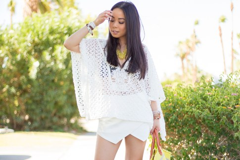 An Dyer wearing Sole Society Citrine OVERSIZED FLORAL NECKLACE, LIV los angeles crochette caftan, Zara White Skort