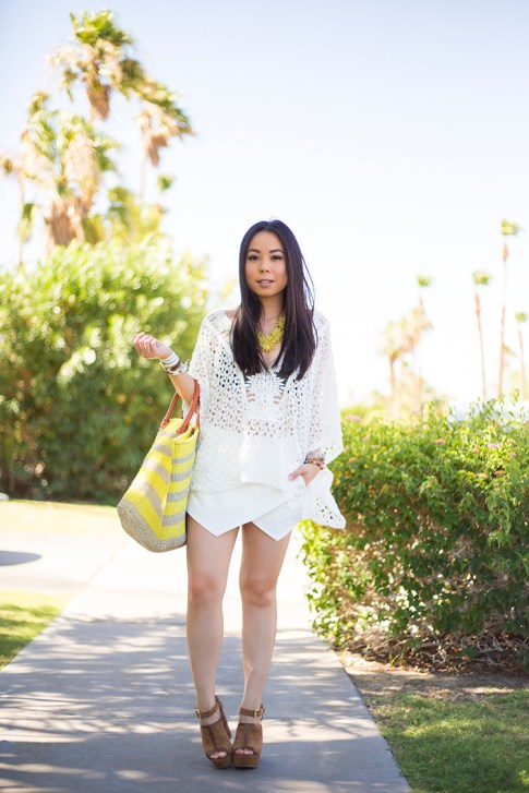 An Dyer wearing Sole Society Keeva Tote, Daniella Wedges and Citrine OVERSIZED FLORAL NECKLACE, LIV los angeles crochette caftan, La Mer Collection Watch, Zara White Skort, Hermes Hapi 3MM