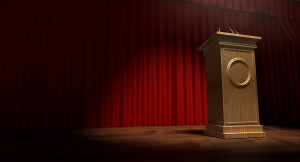 A regular theater stage with closed red curtains and a wooden debate podium lit by a single spotlight