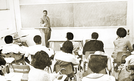 Professor Guy Darnell makes a point to students during an investment class lecture.Richard Gibson, Jr. is seated at the extreme left in front row.