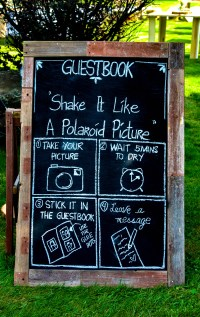 Wooden guestbook sign written by hand in chalk