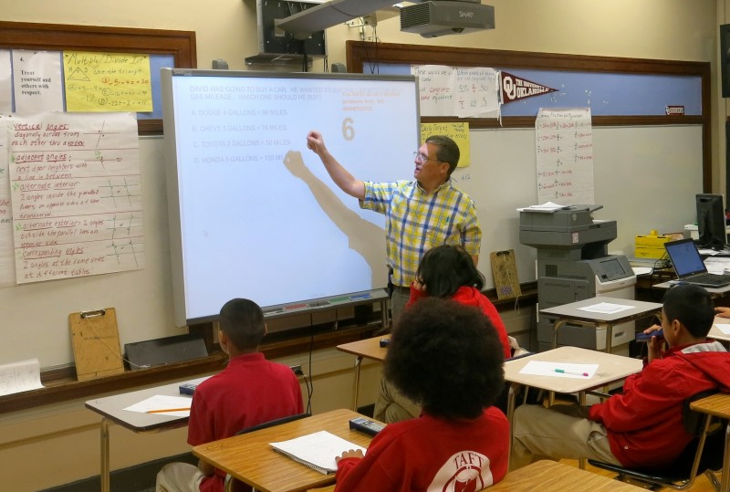 David Woodside, a seventh-grade math teacher at Taft Junior High in Oklahoma City, reviews a problem on the smart board.