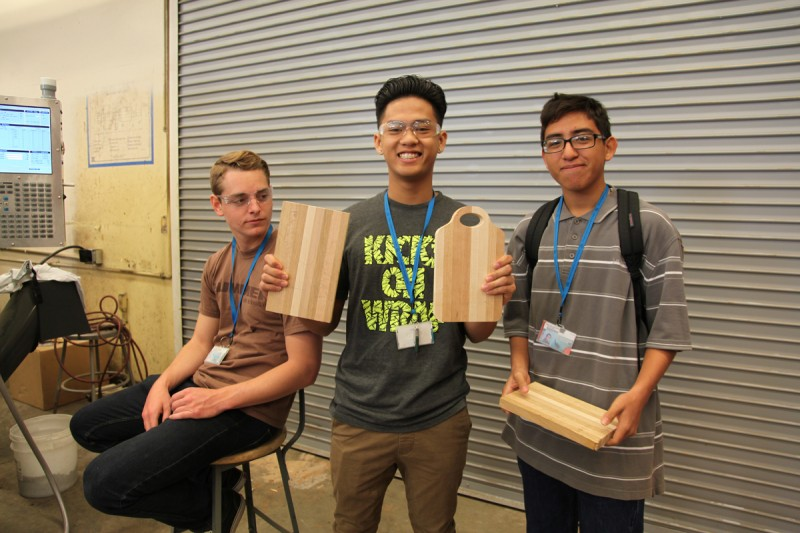 Eleventh graders show off the cheese boards they made in fine woodworking, a class that soon will be phased out, according to the vice principal of Kearny High School's engineering program, James Michaelian.