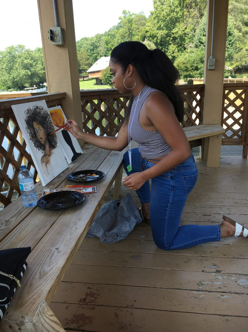 Proctor Institute Intern Krystal Jackson, 21, takes a break from her duties to paint a picture at the Haley Farm lake gazebo.