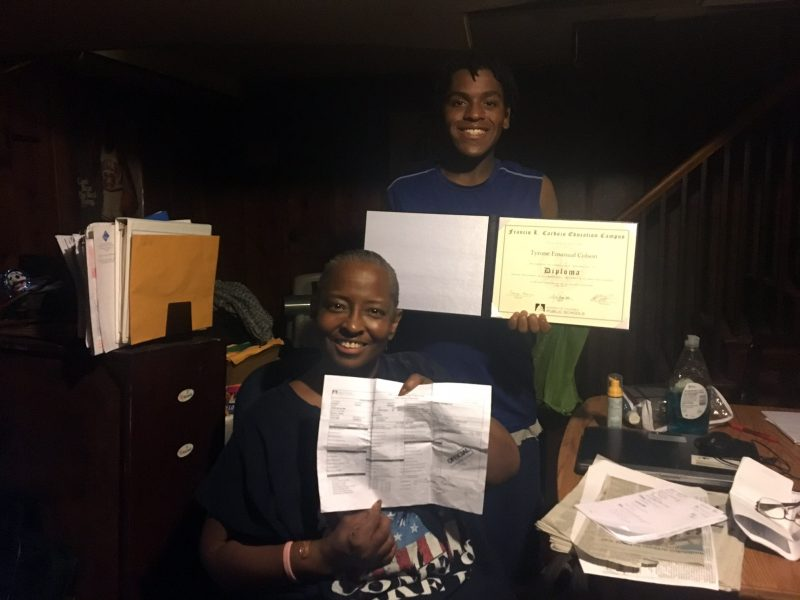 Daisy Brown holds son Tyrone Colson's high school transcript while Colson displays his high school diploma.
