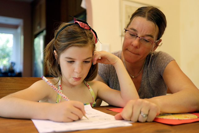"Stacey Jacobson-Francis works on math homework with her 6 year old daughter Luci Wednesday, May 14, 2014, at their home in Berkeley, Calif. As schools around the U.S. implement national Common Core learning standards, parents trying to help their kids with math homework say that adding, subtracting, multiplying and dividing has become as complicated as calculus. Stacey Jacobson-Francis, 41, of Berkeley, California, said her daughter's homework requires her to know four different ways to add. ""That is way too much to ask of a first grader. She can't remember them all, and I don't know them all, so we just do the best that we can,"" she said. (AP Photo)"