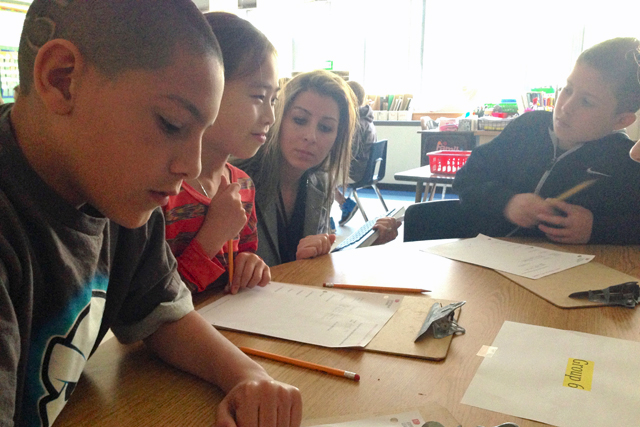 Christina Liberatore, an inclusion teacher at East Moriches Elementary School, helps her fourth-grade students complete a group assignment. (Photo: Amanda M. Fairbanks)