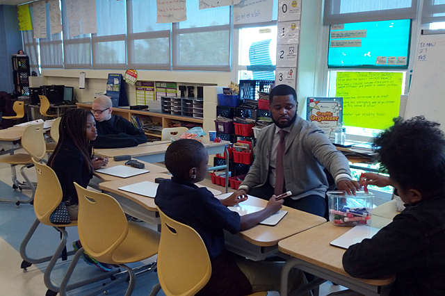 Fourth grade teacher Milton Bryant works with students in a small group during a blended learning session at Ketcham Elementary School. Elsewhere in the classroom students worked with other educators and on computers, and they rotated at intervals to each station. (Photo: Nichole Dobo)