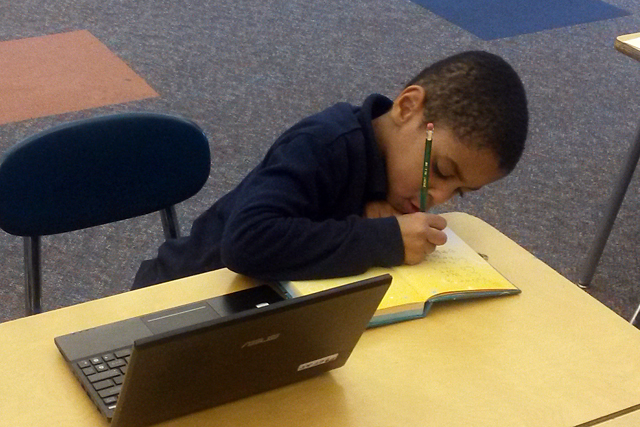 A kindergartener at Brenda Scott Elementary School works on a writing assignment. All students in the Education Achievement Authority use computers for at least part of their day. (Photo: Sarah Butrymowicz)