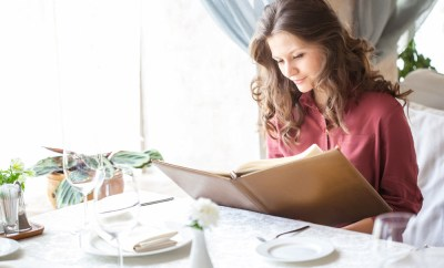 Woman reading menu in fancy restaurant