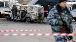 An armed Russian official stands near a burned out police car in St. Petersburg, Russia. FILE PHOTO. EPA/ANATOLY MALTSEV