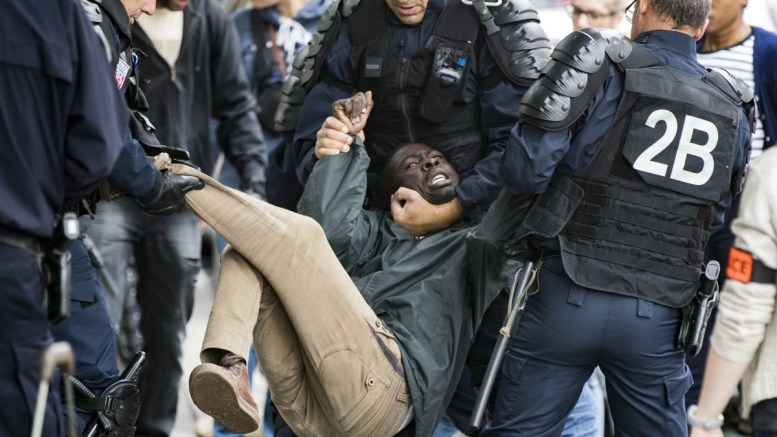FILE PHOTO. A migrant struggles as he is evacuated by the French police.  EPA/ETIENNE LAURENT