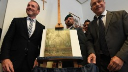 Axel Ruger (L), director of Amsterdam's Van Gogh Museum, stands next to the painting 'Congregation Leaving The Reformed Church of Neunen' by Vincent Van Gogh during an Italian investigators' press conference in Naples, Italy, 30 September 2016. Two priceless Van Goghs stolen from Amsterdam's Van Gogh Museum in December 2002 were among the assets recovered by Italian Finance police from a drug-trafficking clan in the Neapolitan Camorra mafia Friday. The works are worth some $100 million, investigative sources said. The paintings are 'The Beach At Scheveningen During A Storm' (1882) and 'Congregation Leaving The Reformed Church of Neunen' (1884-1885). Some of the gang who stole the Van Goghs and other paintings were arrested a year later but the haul was never found. Assets worth tens of millions of euros were seized from the Camorra group.  EPA/CIRO FUSCO  EPA/CIRO FUSCO