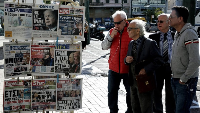 Περαστικοί διαβάζουν τα πρωτοσέλιδα των εφημερίδων σε περίπτερο της Αθήνας. ΑΠΕ-ΜΠΕ, ΣΥΜΕΛΑ ΠΑΝΤΖΑΡΤΖΗ