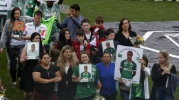 Relatives hold pictures of their late loved ones at the mass memorial service for the 50 Brazilian victims of the 28 November plane crash in Colombia, at the Arena Conda stadium, in Chapeco, Santa Catarina, Brazil, 03 December 2016. The Brazilian victims of the plane crash included 19 Chapecoense players, 25 executives, coaches and special guests of the club and a score of journalists. 71 people died when an aircraft crashed late 28 November 2016 with 77 people on board in a mountainous area outside Medellin, Colombia. Brazilian soccer club Chapecoense were scheduled to play in the Copa Sudamericana final against Medellin's Atletico Nacional on 30 November 2016.  EPA/SEBASTIAO MOREIRA