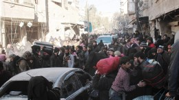 Civilians with their luggage crowd a street in the eastern part of Aleppo, Syria. EPA/GHITH SY