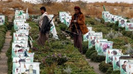 FILE PHOTO: Armed Houthi supporters walk amongst the graves with portraits of late Houthi fighters and supporters allegedly killed in the ongoing conflict in war-affected Arab country, during the Houthi-held Martyr Week anniversary at a cemetery in Sana'a, Yemen. EPA, YAHYA ARHAB