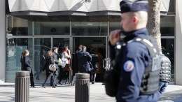 People enter the International Monetary Fund (IMF) headquarters while a police officer stands guard outside in Paris, France, 16 March 2017. An employee of the IMF has been injured in the face after an explosion while opening a letter. EPA, IAN LANGSDON