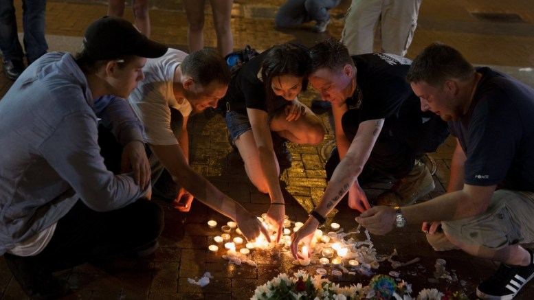 FILE PHOTO: People place candles as they gather during a vigil in Charlottesville, Virginia, USA, 12 August 2017. EPA, TASOS KATOPODIS