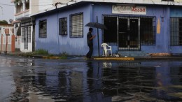 A man protects himself from the rain on an empty street before the imminent passage through the island of Hurricane Irma in San Juan, Puerto Rico, 06 September 2017. Puerto Rico is preparing for the arrival of the category 5 hurricane. EPA/Thais Llorca