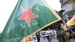 FILE PHOTO. A woman carries a YPG flag, the military unit of the Kurdish party in Syria, during a rally. EPA/AXEL HEIMKEN