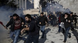 Διαδηλωτές προσπαθούν να προστατευτούν από τα δακρυγόνα που έριξαν αστυνομικοί για να τους απωθήσουν, έξω από την Βουλή, Αθήνα Παρασκευή 12 Ιανουαρίου 2018. ΑΠΕ-ΜΠΕ/ΓΙΑΝΝΗΣ ΚΟΛΕΣΙΔΗΣ