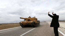 FILE PHOTO. A man waves to Turkish soldiers on tanks near the Syrian-Turkish border, at Reyhanli district in Hatay, Turkey. EPA/SEDAT SUNA