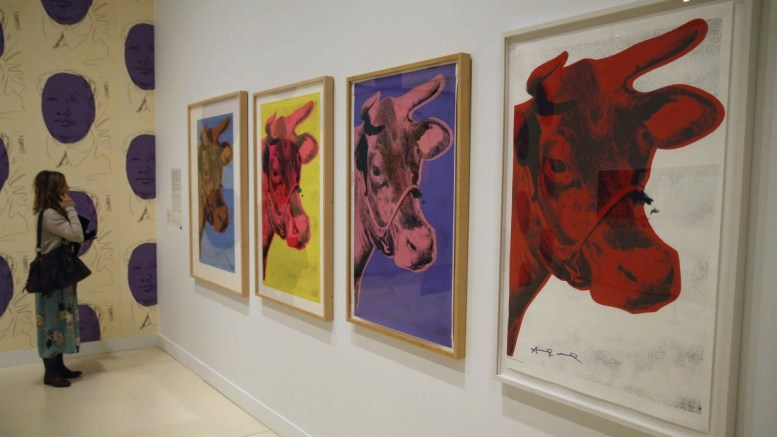 A visitor looks at different versions of US artist Andy Warhol's artwork 'Cow' on display during the press preview of the exhibition 'Andy Warhol. The Mechanical Art' at the CaixaForum in Madrid, Spain, 31 January 2018. The display featuring some 350 works by Warhol will run from 01 February to 06 May. EPA, Paco Campos