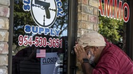 An unidentified person looks through the windows of the Sunrise Tactical Supplies store in Coral Springs, Florida, USA, on 16 February 2018, where Nicolas Cruz reportedly bought the weapon used during the shooting at Marjory Stoneman Douglas High School in Parkland, Florida, EPA, CRISTOBAL HERRERA