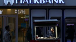A street vendor in front of the Turkish Halkbank, in Istanbul. Mehmet Hakan Atilla, 47, a deputy manager at Halkbank, has been found guilty by a federal court in New York of participating in a major scheme in which Iranian gold and gas where traded for food and gold. EPA, SEDAT SUNA