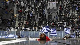A woman on a balcony of a hotel holds a Greek flag as protesters on a street take part in a massive rally over the name of the Former Yugoslav Republic of Macedonia (FYROM) against to its use of the name 'Macedonia' amid a revival of efforts to find a solution between the two countries, in Athens, Greece, 04 February 2018. EPA, YANNIS KOLESIDIS