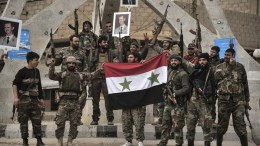 File Photo: An undated handout photo showing Syrian army soldiers with their allied members from Hezbollah celebrate the victory in the vicinity of Al-Boukamal city in the countryside of Deir Ezzor, Syria. EPA, SANA HANDOUT, EDITORIAL USE ONLY