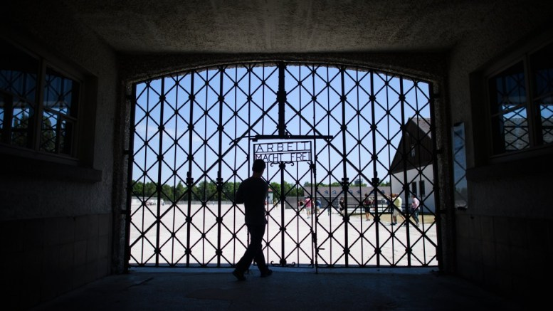 A visitor walks behind a replica of the notorious iron gate with the slogan 'Arbeit macht frei' ('Work will set you free') at the museum of the Nazi concentration camp memorial site in Dachau, near Munich, southern Germany, EPA, CHRISTIAN BRUNA