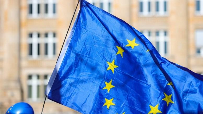File Photo: An EU flag fly over as participants gather in a rally. EPA, ARMANDO BABANI