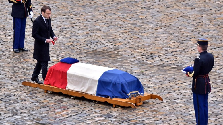 French President Emmanuel Macron (L) pays respect in front of the flag-drapped coffin during a national ceremony for Lieutenant-Colonel Arnaud Beltrame at the Hotel des Invalides in Paris, France, on 28 March 2018. EPA, CHRISTOPHE PETIT TESSON