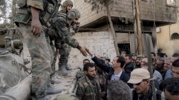 A handout photo made available by the official Syrian Arab News Agency (SANA) shows Syrian President Bashar Al-Assad (C) meeting with Syrian Arab Army soldiers, in Eastern Ghouta in Damascus Countryside, Syria, 18 March 2018.  EPA, SANA HANDOUT HANDOUT HANDOUT EDITORIAL USE ONLY, NO SALES