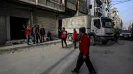 Volunteers with Syrian Arab Red Crescent (SARC) unload aid trucks in Douma, in Eastern Ghouta, Syria, 05 March 2018. A convoy of aid supplies reach the besieged community in Eastern Ghouta for the first time in weeks and after months of bombardment. EPA, Mohammed Badra
