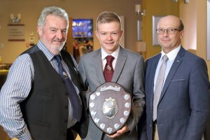 John Gill, chairman of the NI Hereford Breeders' Association, presenting Marcus Murdoch, Newry, along with his father Robert, the young handler trophy at the association's annual dinner, Enniskillen. Picture: Cliff Donaldson