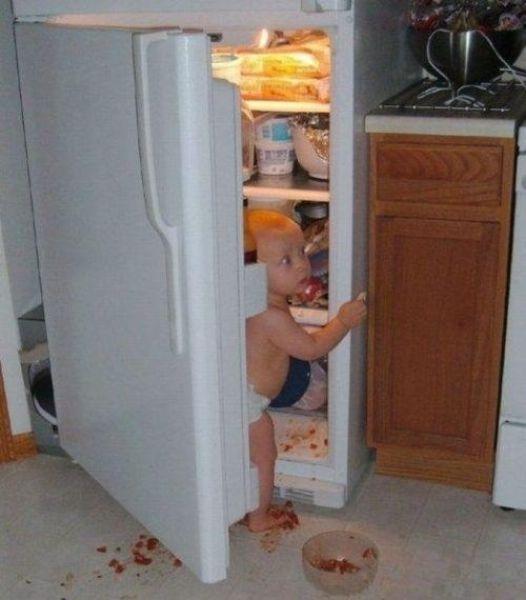 Criança abrindo a portada geladeira e com a cara suja de comida.