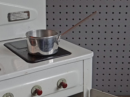 Metal toy saucepan on the vintage Amersham toy cooker