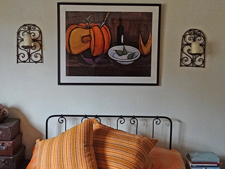 Bernard Buffet vintage print above a wrought iron bed