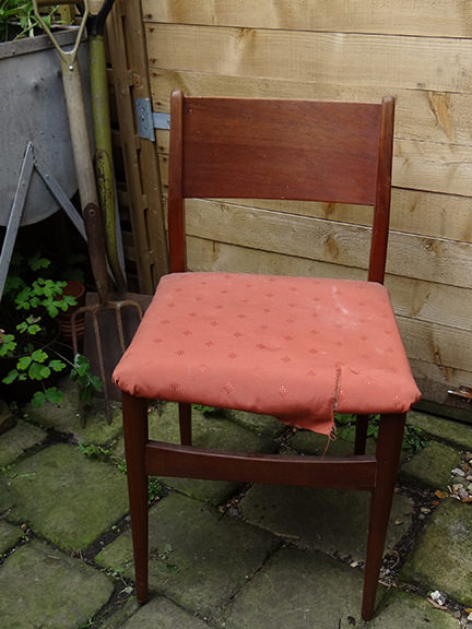 ripped seat cover on a teak chair