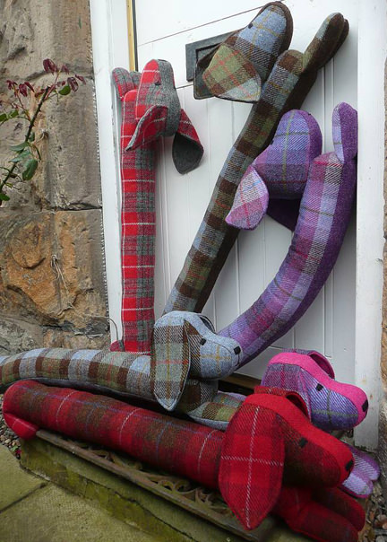 multicoloured collection of dashund shaped, Harris tweed draught excluders handmade in Harris tweed by Queenie on Notonthehighstreet
