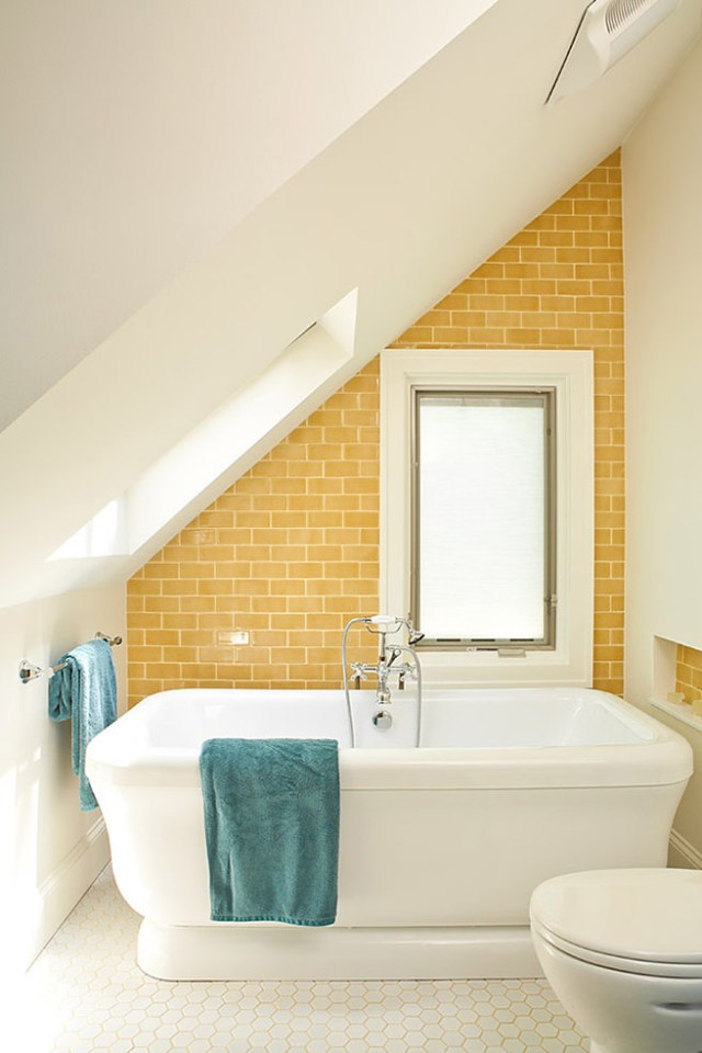 Mustard tiled bathroom with blue-green towels