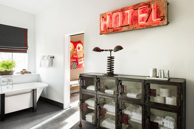 Red 'hotel' neon sign in vintage industrial decorated bathroom