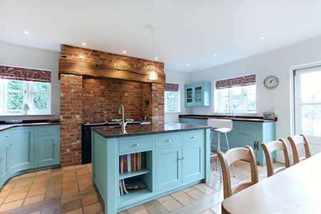 Blue painted fitted kitchen with red brick stove alcove and terracotta floor